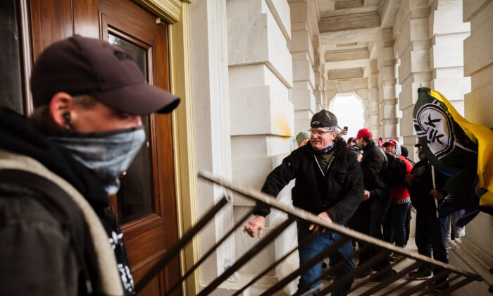 Protesters bash an entrance of the Capitol building in Washington on Jan. 6, 2021. (Jon Cherry/Getty Images)