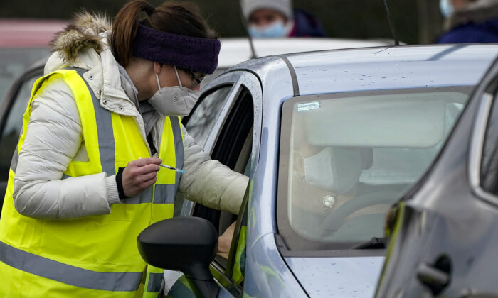 A man sits in his car as he is administered the Pfizer/BioNTech CCP virus vaccine at a drive-thru COVID-19 vaccination centre in Hyde, England, on Jan. 8, 2021. (Christopher Furlong/Getty Images)
