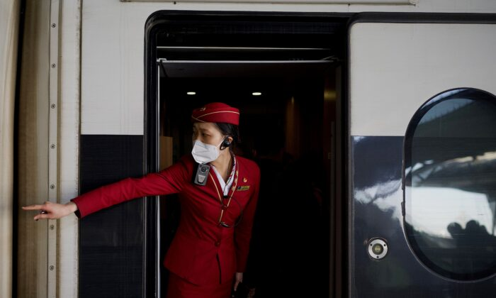 A train attendant signals to passengers to get in at Wuhan railway station on New Year's Eve in Wuhan in Chinas central Hubei province on Dec. 31, 2020. (Noel Celis/AFP via Getty Images)