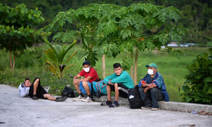 Honduran migrants, part of a U.S.-bound caravan, rest after being intercepted by Guatemalan Army members in San Luis, Peten department, Guatemala on Oct. 3, 2020. (Johan Ordonez/AFP via Getty Images)