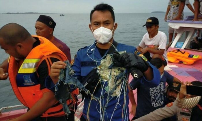 A member of the rescue team looking for an Indonesian plane that lost contact after taking off from the capital Jakarta holds suspected debris, at sea, Jan. 9, 2021. (Instagram @humasjakrire/via Reuters)