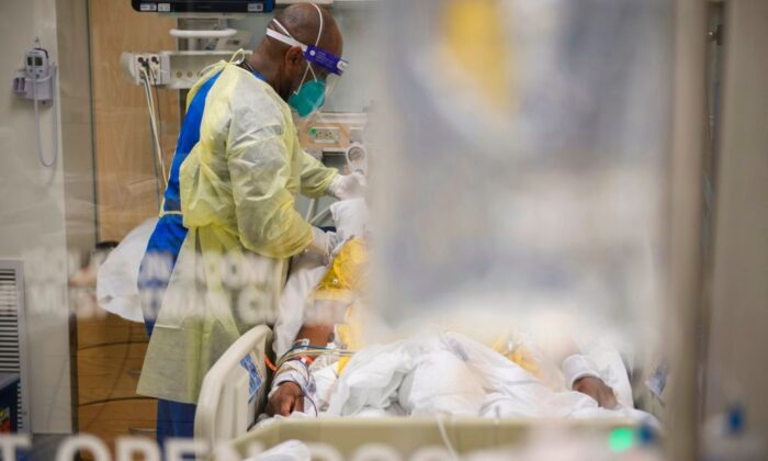 Nurses wearing personal protective equipment (PPE) attend to patients in a Covid-19 intensive care unit (ICU) at Martin Luther King Jr. (MLK) Community Hospital on January 6, 2021. (PATRICK T. FALLON/AFP via Getty Images)