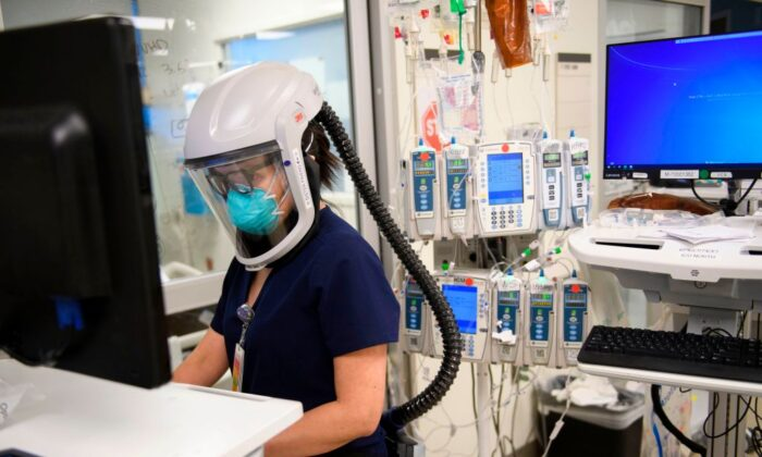 A nurse wearing personal protective equipment, including a personal air purifying respirator, works in a COVID-19 intensive care unit at Martin Luther King Jr. (MLK) Community Hospital on Jan. 6, 2021. (PATRICK T. FALLON/AFP via Getty Images)