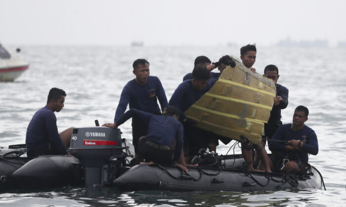 Indonesian Navy divers pull out a part of an airplane out of the water during a search operation for the Sriwijaya Air passenger jet that crashed into the sea near Jakarta, Indonesia, on Jan. 10, 2021. (Achmad Ibrahim/AP Photo)