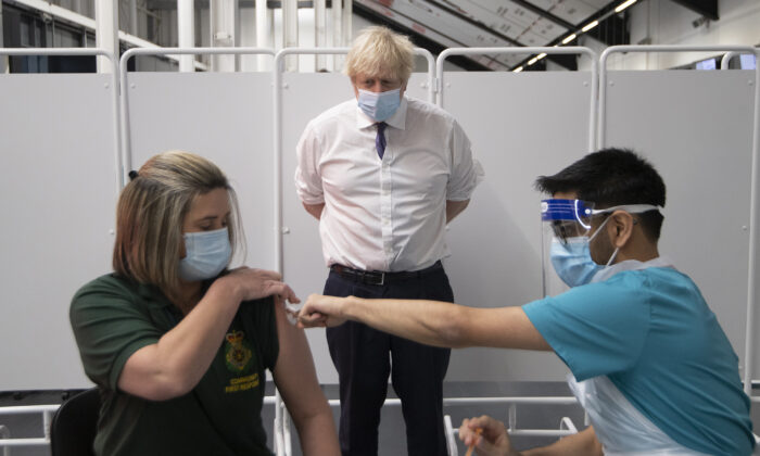 Prime Minister Boris Johnson watches first responder Caroline Cook getting her vaccination as he visits a vaccination centre at Ashton Stadium in Bristol, England, on Jan. 11, 2021. (Eddie Mulholland/WPA Pool/Getty Images)