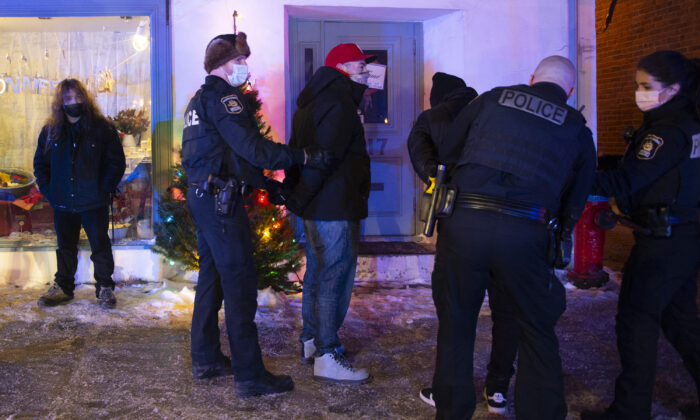 Police arrest two men in Quebec City for breaking a new curfew in the province of Quebec, Canada, on Jan. 9, 2021. (Jacques Boissinot/The Canadian Press)