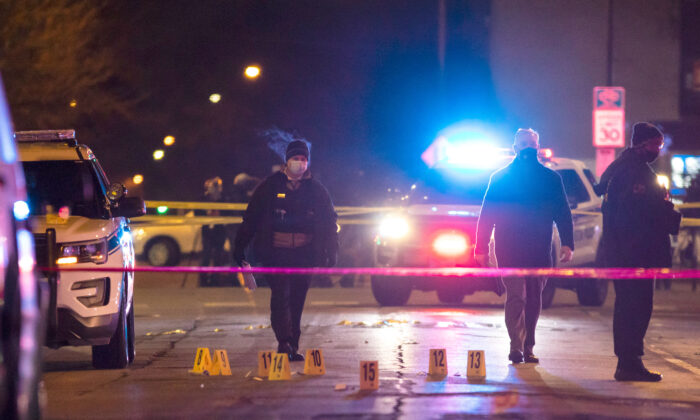 Chicago and Evanston police investigate a crime scene after a gunman went on a shooting spree before being killed by police during a shootout in Evanston, Ill., on Jan. 9, 2021. (Ashlee Rezin Garcia/Chicago Sun-Times via AP)