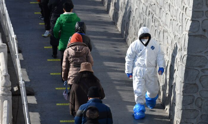 A health worker walks past residents as they line up to be tested for the COVID-19 in Beijing, on Jan. 11, 2021 (GREG BAKER/AFP via Getty Images)