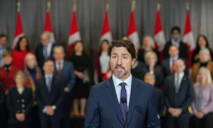 Prime Minister Justin Trudeau stands in front of his cabinet as he speaks to media during the final day of the Liberal cabinet retreat at the Fairmont Hotel in Winnipeg, on Jan. 21, 2020. (Mike Sudoma/The Canadian Press)
