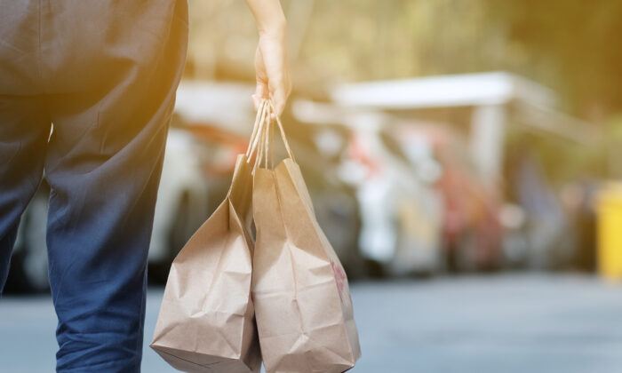 A woman carries a takeout order as restaurants remain closed for indoor dining due to pandemic restrictions. (Getty Images)