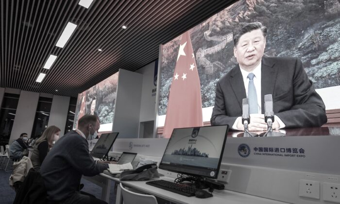 Journalists sit next to the screens showing Chinese leader Xi Jinping delivering a speech via video for the opening ceremony of the 3rd China International Import Expo at a media center in Shanghai on Nov. 4, 2020. (STR/AFP via Getty Images)