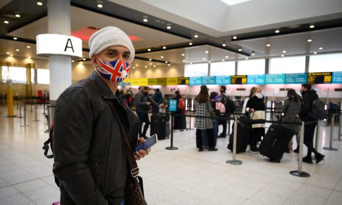 A passenger wearing a Union Flag face mask waits to board one of the few flights departing at Gatwick Airport in London, on Nov. 27, 2020. (Leon Neal/Getty Images)