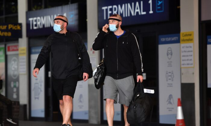 Passengers wearing a face mask or covering due to the COVID-19 pandemic, react as they exit Terminal 1 after landing at Manchester Airport, northwest England, on July 27, 2020. (Anthony Devlin/AFP via Getty Images)