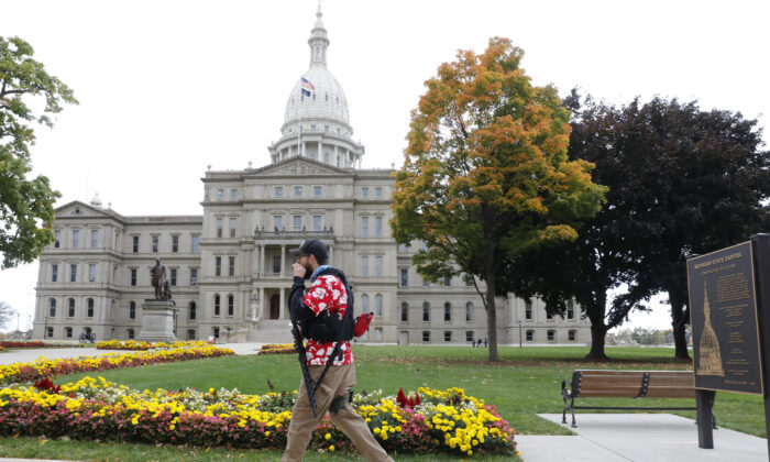 A man carries a firearm outside the Michigan State Capitol in Lansing, Mich., on Oct. 17, 2020. (Jeff Kowalsky/AFP/Getty Images)