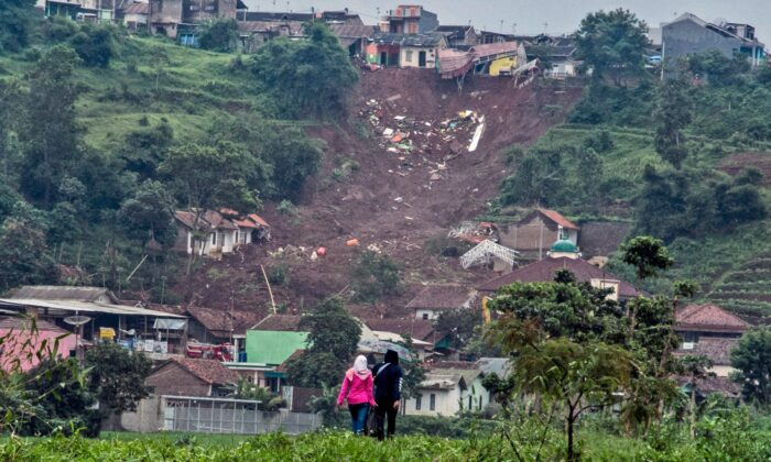 People walk past the site where a village was hit by landslides in Sumedang, West Java, Indonesia, on Jan. 11, 2021. (Sorasoca/AP Photo)