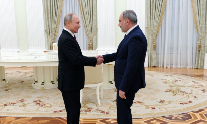 Russian President Vladimir Putin (L) shakes hands with Armenian Prime Minister Nikol Pashinyan before a meeting with leaders of Armenia and Azerbaijan over the disputed Nagorno-Karabakh region's future at the Kremlin in Moscow on Jan. 11, 2021. (Mikhail Klimentyev/SPUTNIK/AFP via Getty Images)