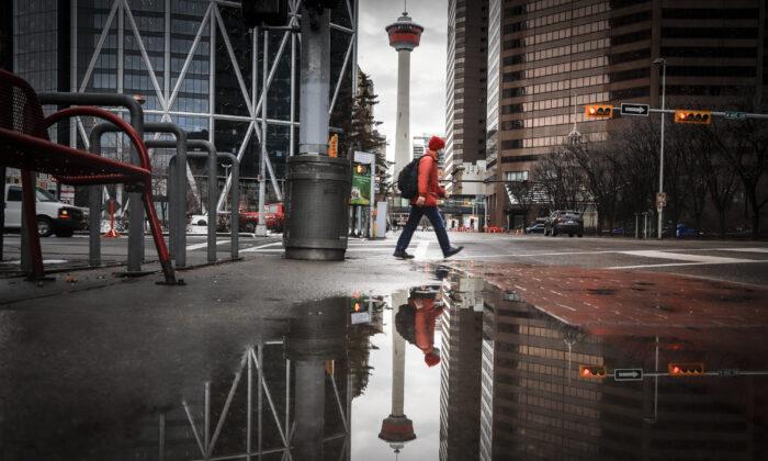 A pedestrian walks through an empty downtown Calgary on Dec. 9, 2020. (The Canadian Press/Jeff McIntosh)
