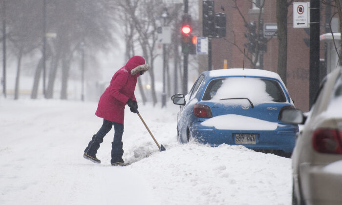 A woman shovels snow away from her car during the first heavy snowfall of the season in Montreal, Canada on Jan. 2, 2021. (Graham Hughes/The Canadian Press)