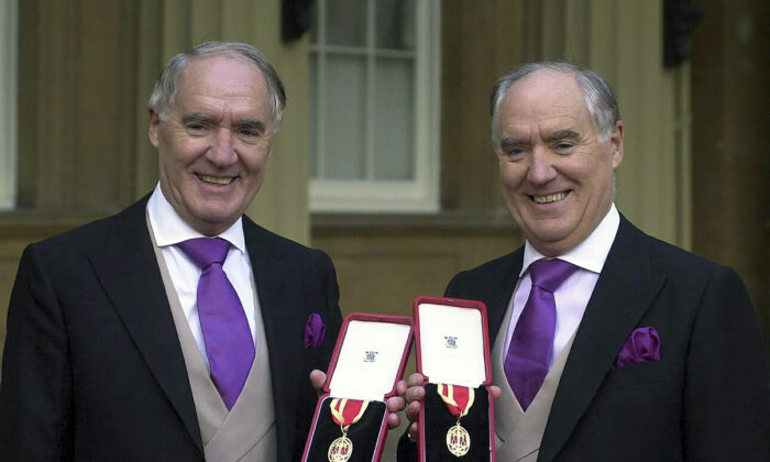 Multi-millionaires David Barclay (L) stands with his twin brother Frederick Barclay, after receiving their knighthoods from the Queen at Buckingham Palace in London, on Oct. 31, 2000. (Michael Stephens/PA via AP)