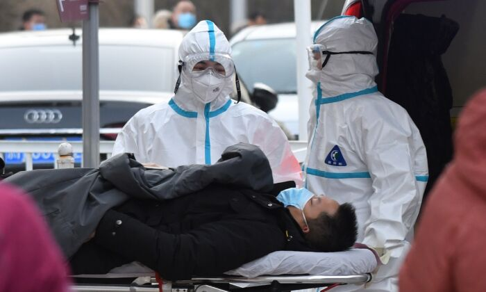 Medical workers deliver a patient to the fever clinic at a hospital in Beijing, on Jan. 13, 2021. (GREG BAKER/AFP via Getty Images)