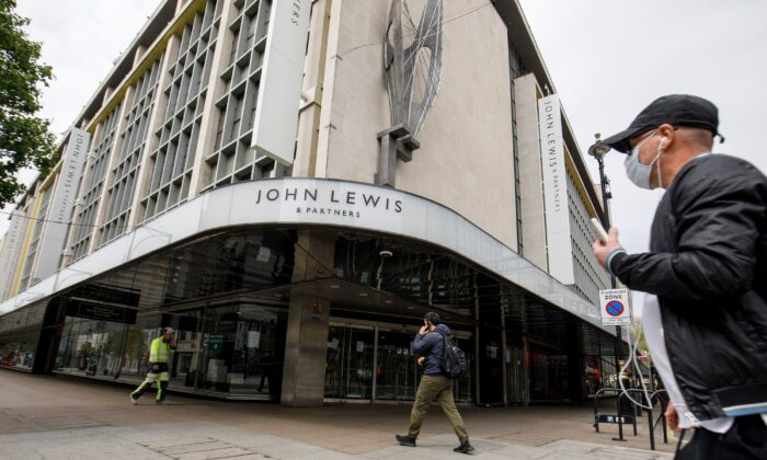 A man walks past a John Lewis department store, closed-down due to lockdown laws, on Oxford Street in central London on April 27, 2020. (Tolga Akmen/AFP via Getty Images)