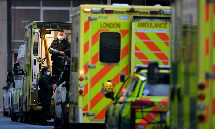A paramedic works in the back of an ambulance, parked outside the Royal London hospital in London on Jan. 12, 2021 as surging cases of the novel coronavirus are placing health services under increasing pressure. (DANIEL LEAL-OLIVAS/AFP via Getty Images)