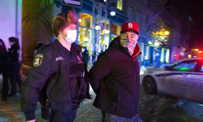 A man is arrested by police after 8 p.m. as a curfew begins in the province of Quebec to counter the spread of COVID-19 on Jan. 9, 2021 in Quebec City. (Jacques Boissino/The Canadian Press)