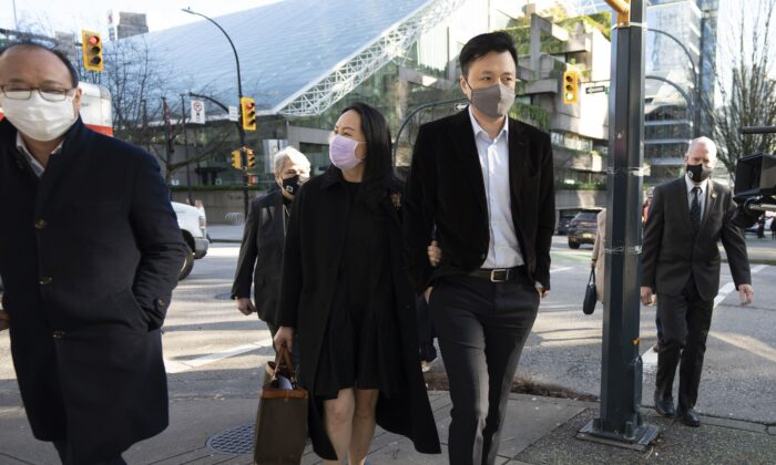 Huawei CFO Meng Wanzhou leaves the B.C. Supreme Court with her husband, Liu Xiaozong, during a break from an extradition hearing in Vancouver Jan. 13, 2021. (The Canadian Press/Jonathan Hayward)