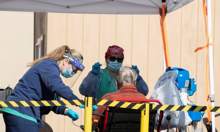 Health care workers attending to a patient as St. Mary Medical Center resort to using triage tents outside to handle the overflow at its 200 bed hospital during the outbreak of the CCP virus in Apple Valley, Calif., on Jan. 12, 2021. (Mike Blake/Reuters)