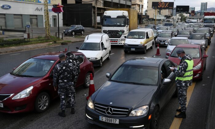 Police officers stand at a checkpoint to inspect cars that violate COVID-19 lockdown measures in Beirut, Lebanon, on Jan. 14, 2021. (Bilal Hussein/AP Photo)