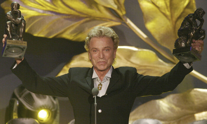 """German illusionist Siegfried Fischbacher of the duo """" Siegfried & Roy"""" holds their trophies after receiving the World Entertainment Award at the World Award 2003 ceremony in Hamburg, Germany, on Oct. 22, 2003. (Fabian Bimmer/AP Photo File)"""