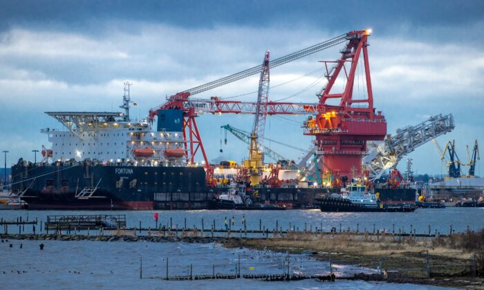"""Tugboats get into position on the Russian pipe-laying vessel """"Fortuna"""" in the port of Wismar, Germany, on Jan 14, 2021. The special vessel is being used for construction work on the German-Russian Nord Stream 2 gas pipeline in the Baltic Sea. (Jens Buettner/dpa via AP)"""
