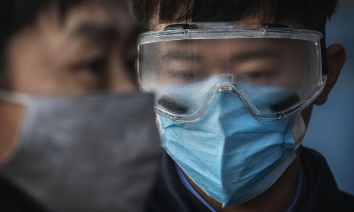 A Chinese railway worker has fogged safety goggles as he waits to check the temperature of arriving passengers at a train station in Beijing, on Jan. 31, 2020. (Kevin Frayer/Getty Images)