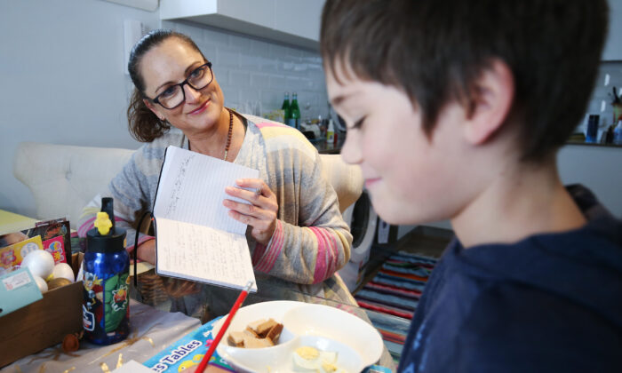 Donna Eddy helps her son Phoenix with school work at their home in Sydney, Australia on April 9, 2020. (Brendon Thorne/Getty Images)
