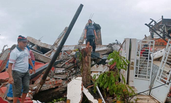 Residents inspect earthquake-damaged houses in Mamuju, West Sulawesi, Indonesia on Jan. 15, 2021. (Rudy Akdyaksyah/AP Photo)