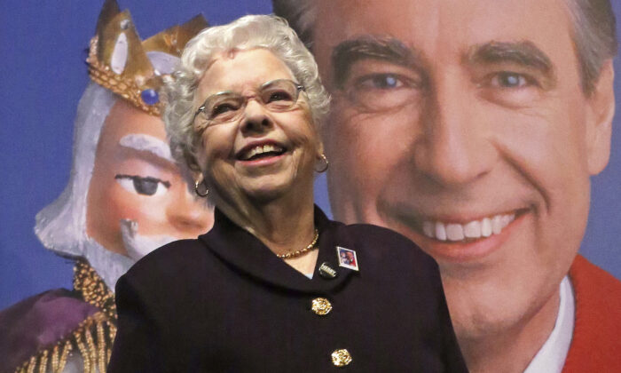Joanne Rogers stands in front of a giant Mister Rogers Forever Stamp in Pittsburgh on March 23, 2018. (AP Photo/Gene J. Puskar)