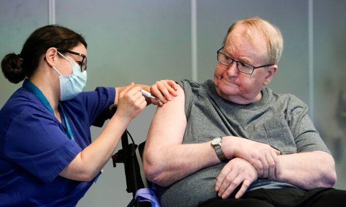 Svein Andersen, 67 years-old resident of 'Ellingsrud home' and first in Norway to receive the vaccine is given the Pfizer-Biontech Covid-19 corona virus vaccine by Nurse Maria Golding in Oslo, Norway, on Dec. 27, 2020. (Fredrik Hagen/NTB/AFP via Getty Images)
