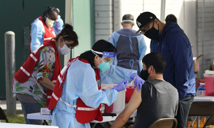 Health care workers receive a COVID-19 vaccination at Ritchie Valens Recreation Center in Pacoima, Calif., on Jan. 13, 2021. (Marcio Jose Sanchez/AP Photo)