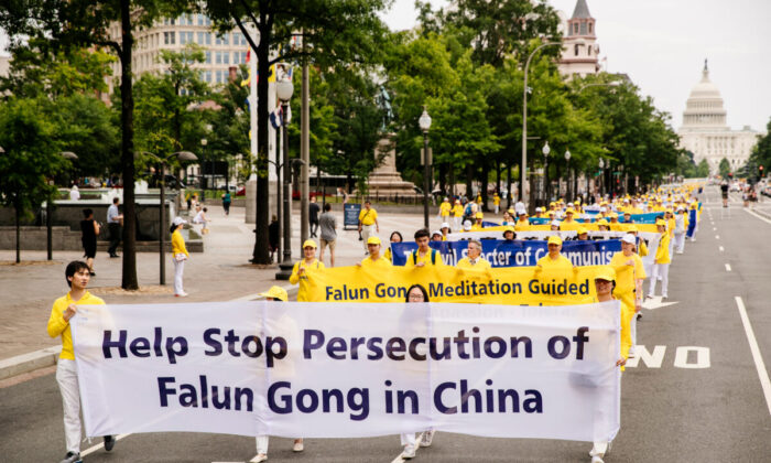 Falun Gong practitioners take part in a grand march calling for an end to the persecution of Falun Gong in China, in Washington on June 20, 2018. (Edward Dye/The Epoch Times)