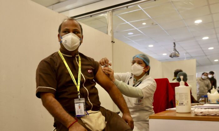 A health worker (L), receives a COVID-19 vaccine at a private Hospital in New Delhi, India, on Jan. 16, 2021. (Manish Swarup/AP Photo)