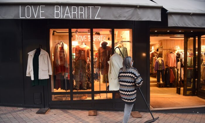 A shopkeeper closes her store, in Biarritz, southwestern France, on Jan. 16, 2021. (Gaizka Iroz/AFP via Getty Images)
