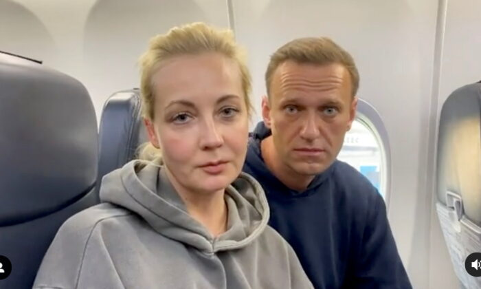 Russian opposition leader Alexei Navalny and his wife Yulia Navalnaya are seen on board a plane before the departure for the Russian capital Moscow at an airport in Berlin, Germany, on Jan. 17, 2021. (Maria Vasilyeva/Reuters)