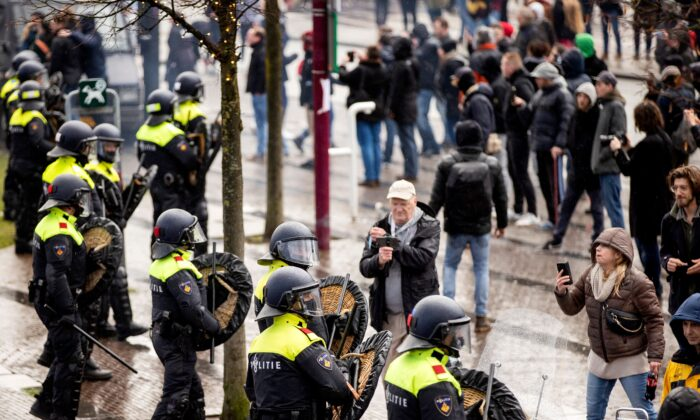 Dutch riot police stand near anti-government activists as they denounce ongoing restrictions related to the coronavirus disease (COVID-19) pandemic among other issues in Museumplein, Amsterdam, on Jan. 17, 2021. (Robin van Lonkhuijsen/ANP/AFP via Getty Images)