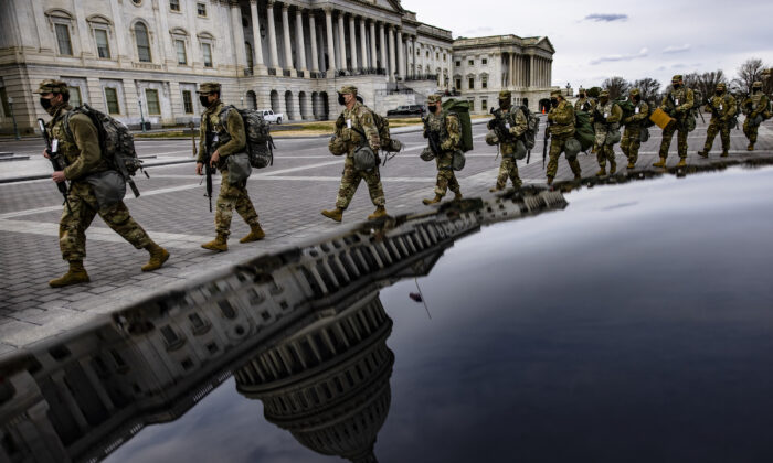Virginia National Guard soldiers march across the east from of the U.S. Capitol on their way to their guard posts in Washington on Jan. 16, 2021. (Samuel Corum/Getty Images)