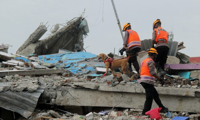 Indonesian police officers with a K9 unit sniffer dog inspect a collapsed hospital building following an earthquake in Mamuju, West Sulawesi province, Indonesia, on Jan. 17, 2021. (Akbar Tado/Antara Foto via Reuters)