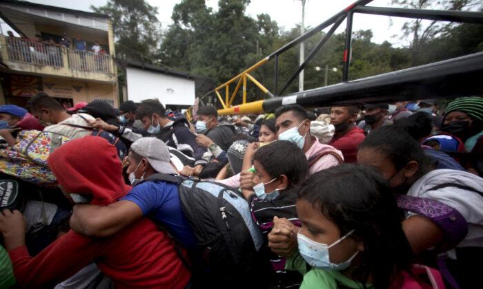 Honduran migrants hoping to reach the U.S. cross the border patrolled by Guatemalan soldiers, in El Florido, Guatemala, on Jan. 16, 2021. (Sandra Sebastian/AP Photo)
