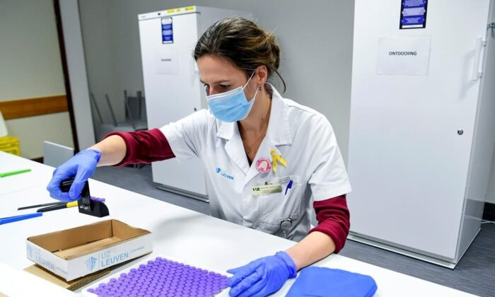 A health worker inspects vials of the Pfizer-BioNTech COVID-19 vaccine as they are thawed in a lab at the UZ Leuven hospital in Leuven, Belgium, on Dec. 27, 2020. (The Canadian Press/Frederic Sierakowski, Pool via AP)