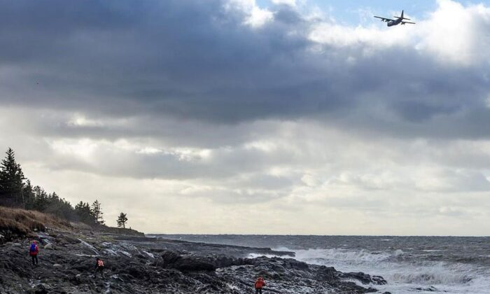 An RCAF Hercules aircraft scours the waters as members of a ground search and rescue team walk along the shore of the Bay of Fundy in Hillsburn, N.S., in an area where empty life-rafts from a scallop fishing vessel were reported on Dec. 15, 2020. (Andrew Vaughan/The Canadian Press)