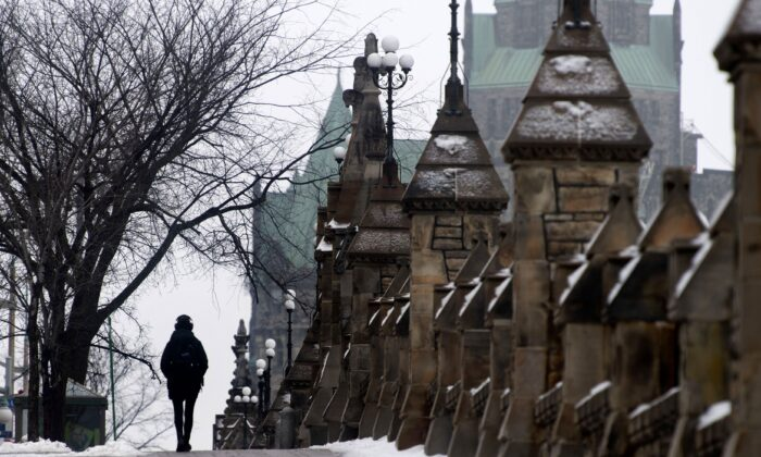 A person walks along the sidewalk next to Parliament Hill in Ottawa on Jan. 14, 2021. (The Canadian Press/Adrian Wyld)
