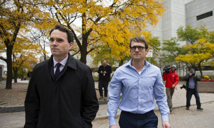 Cameron Ortis (R), a former senior intelligence official with the RCMP charged with violating the Security of Information Act and breach of trust, leaves the courthouse in Ottawa with his lawyer after being granted bail on Oct. 22, 2019. (The Canadian Press/Justin Tang)